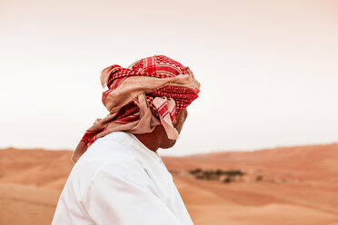 Bedouin in National dress standing in the desert, rear view, Wahiba Sands, Oman - WVF01411
