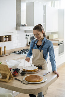 Young woman preparing a cream cake, using tablet - GIOF06203