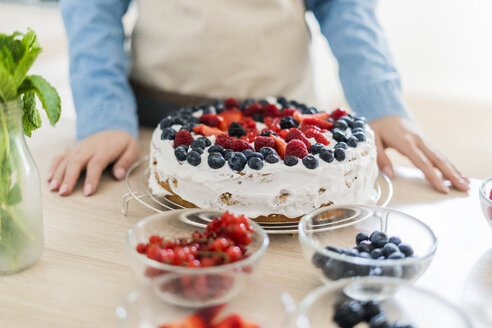 Young woman preparing a cream cake with fresh fruits - GIOF06206
