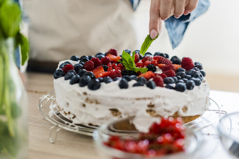 Young woman preparing a cream cake with fresh fruits - GIOF06209