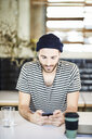 Young man wearing a beanie using cell phone - FMKF05568