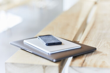 Stack of mobile devices on wooden bench - FMKF05583