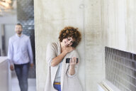 Smiling woman using cell phone at concrete wall with man in background - FMKF05598