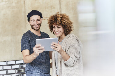 Happy man and woman sharing tablet - FMKF05601