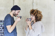 Man and woman drinking coffee and smiling at each other - FMKF05604
