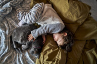 Toddler girl and grey cat sleeping on bed, top view - GEMF02917