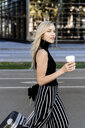 Portrait of smiling blond woman with coffee to go and wheeled luggage - GIOF06214