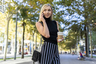 Portrait of smiling blond woman with coffee to go on the phone - GIOF06217