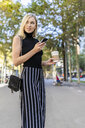 Portrait of smiling blond woman with coffee to go and cell phone - GIOF06220