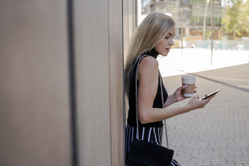 Young blond woman with coffee to go leaning against wall looking at cell  phone - GIOF06223