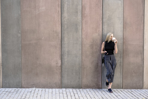 Young blond woman with cell phone leaning against wall drinking coffee to go - GIOF06226
