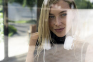 Portrait of smiling blond woman with headphones behind windowpane - GIOF06232