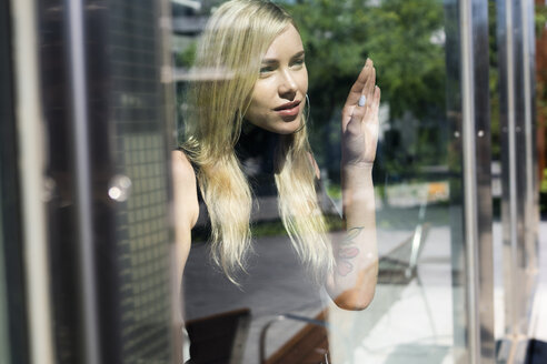 Portrait of blond young woman looking out of window - GIOF06235