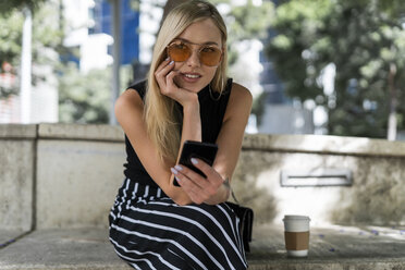 Portrait of blond young woman with cell phone sitting on a wall looking at distance - GIOF06238