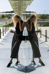 Blond young woman with coffee to go on the phone - GIOF06241