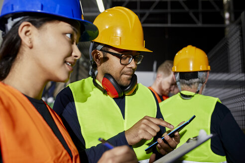 Male and female worker with clipboard and tablet talking in factory - ZEDF02079