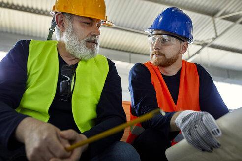 Two men working on plan in factory - ZEDF02088