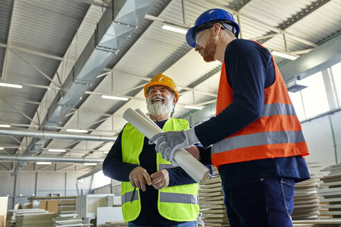 Laughing worker with colleague in factory - ZEDF02091