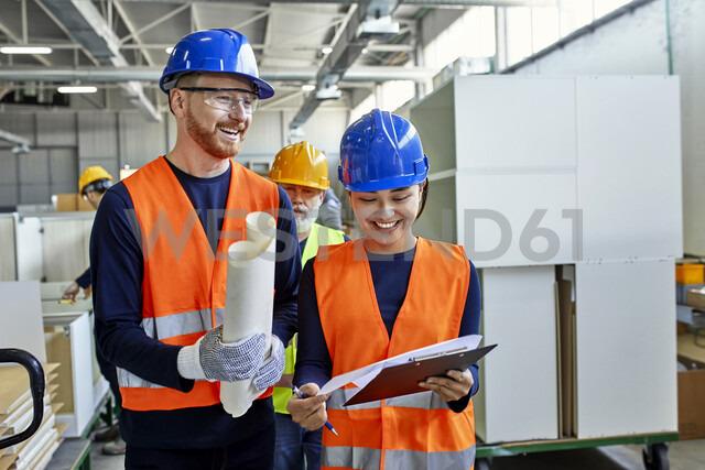 Happy colleagues in protective workwear talking in factory - ZEDF02100 - Zeljko Dangubic/Westend61