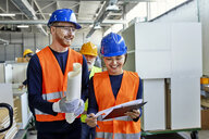 Happy colleagues in protective workwear talking in factory - ZEDF02100