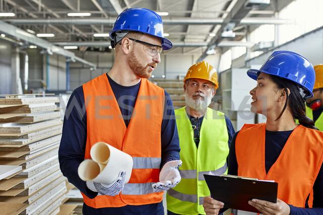 Colleagues in protective workwear talking in factory - ZEDF02103 - Zeljko Dangubic/Westend61