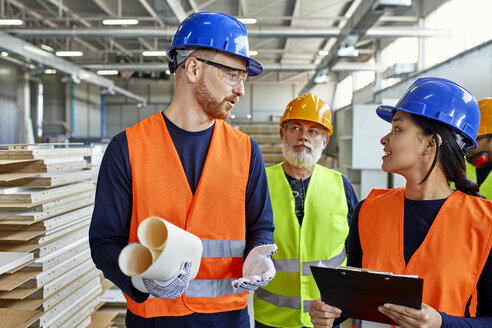 Colleagues in protective workwear talking in factory - ZEDF02103