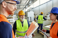Happy colleagues in protective workwear talking in factory - ZEDF02106