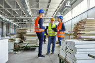 Colleagues in protective workwear talking in factory - ZEDF02109