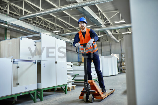 Worker riding on pallet jack in factory - ZEDF02115 - Zeljko Dangubic/Westend61