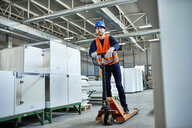 Worker riding on pallet jack in factory - ZEDF02115