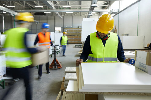 Worker examining wooden boards in factory with colleagues moving in background - ZEDF02118