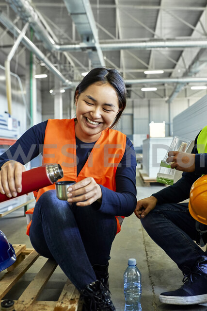 Happy female worker pouring drink into mug during lunch break in factory - ZEDF02133 - Zeljko Dangubic/Westend61