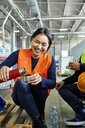 Happy female worker pouring drink into mug during lunch break in factory - ZEDF02133