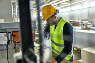 Worker operating drill in factory - ZEDF02142