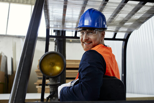 Portrait of smiling worker on forklift in factory - ZEDF02148