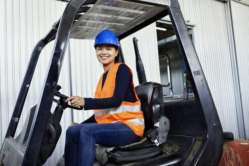 Portrait of confident female worker on forklift in factory - ZEDF02151