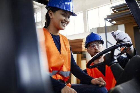Man instructing female worker on forklift in factory - ZEDF02154