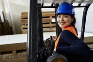 Portrait of confident female worker on forklift in factory - ZEDF02157