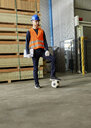 Worker standing in factory warehouse with football - ZEDF02172