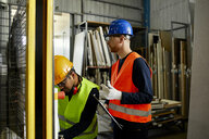 Two men operating machine in industrial factory - ZEDF02175