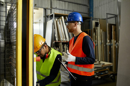 Two men operating machine in industrial factory - ZEDF02175