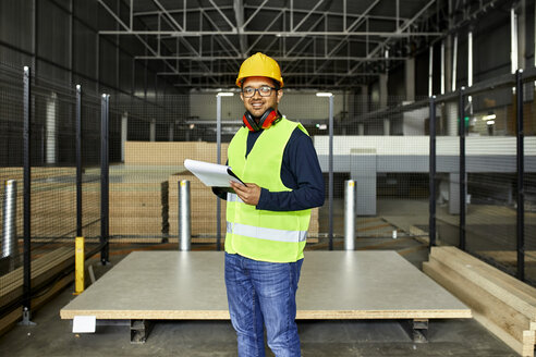 Portrait of smiling worker with clipboard in factory warehouse - ZEDF02196