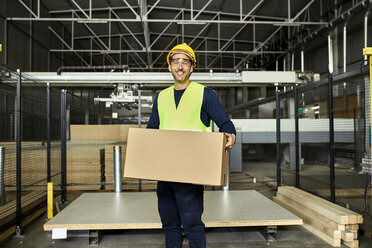 Portrait of smiling worker carrying box in factory warehouse - ZEDF02202