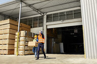 Two workers with box walking on factory yard - ZEDF02217