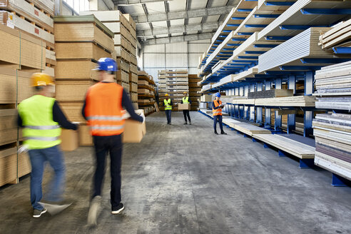 Workers moving and carrying boxes in factory warehouse - ZEDF02220