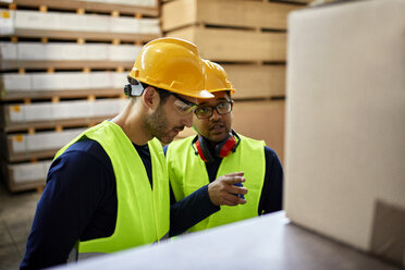 Two workers talking in factory warehouse - ZEDF02226