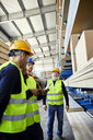 Workers talking in factory warehouse - ZEDF02229