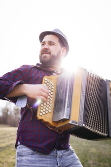 Man with black beard and hat playing the accordion, outside on a meadow, Lower Austria - HMEF00342