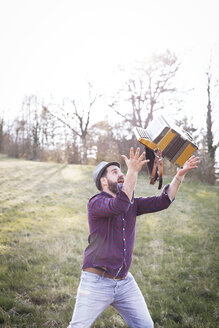 Bearded man throwing accordion in the air on a meadow - HMEF00345