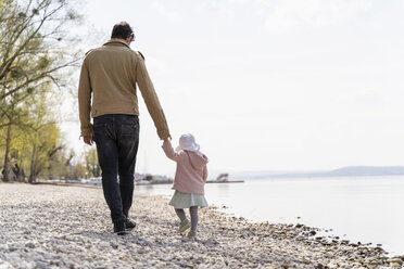 Germany, Bavaria, Herrsching, father and daughter walking on pebble beach at lakeshore - DIGF06742
